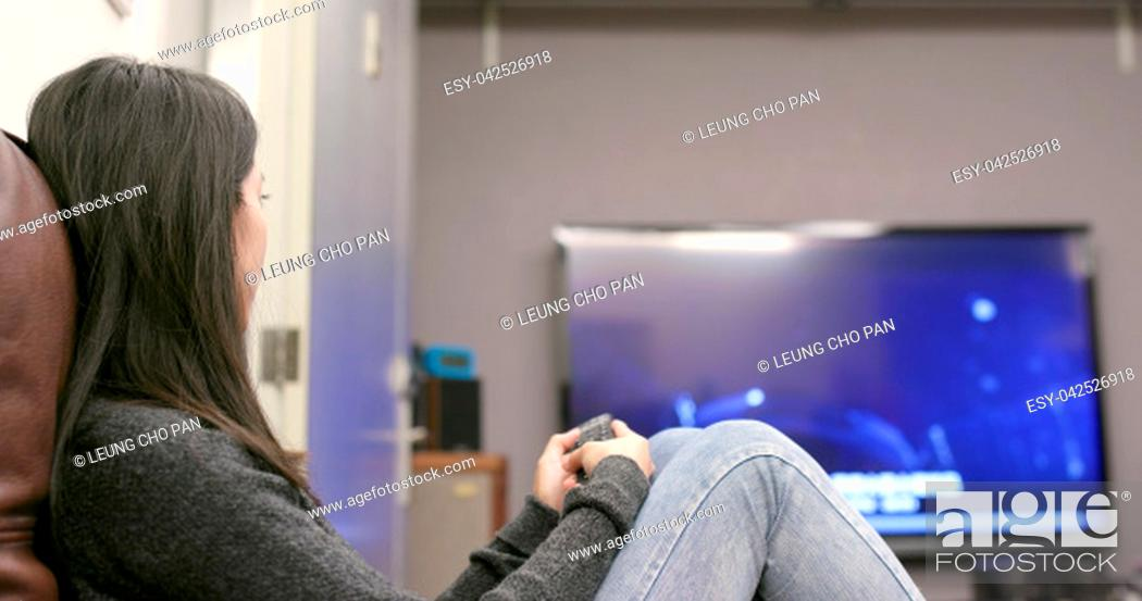 Stock Photo: Woman watching tv at home.