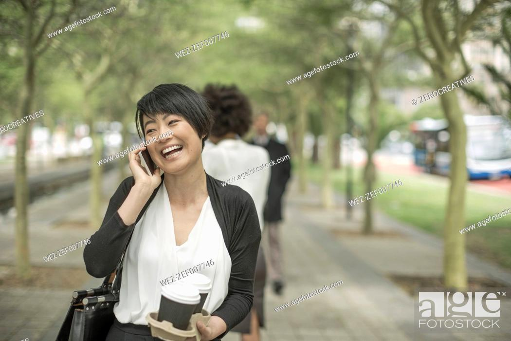 Imagen: Young Asian woman carrying takeaway coffee and talking on the phone.