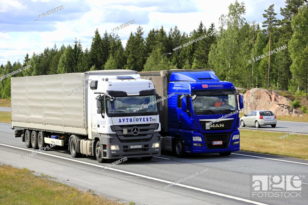 Stock Photo: Blue MAN semi truck overtakes another truck on motorway in summer. Trucks with heavy cargo can be much slower uphill. Salo, Finland - June 8, 2018.