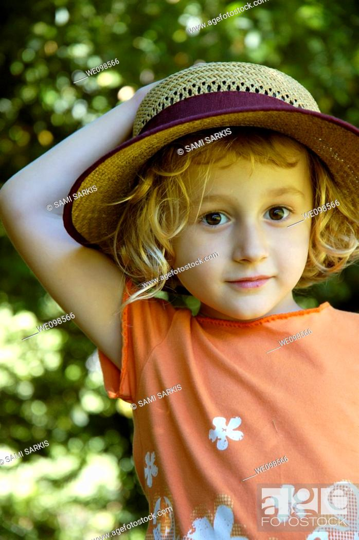 Stock Photo: Little girl wearing a straw hat, Provence, France.