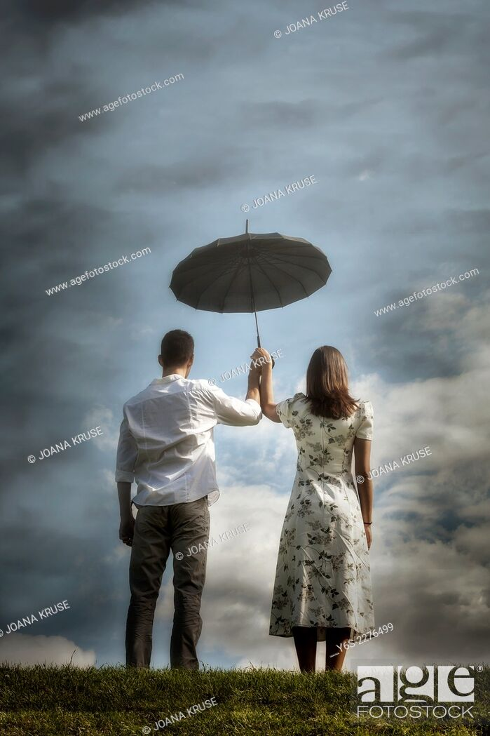 Stock Photo: a couple on a meadow with an umbrella.