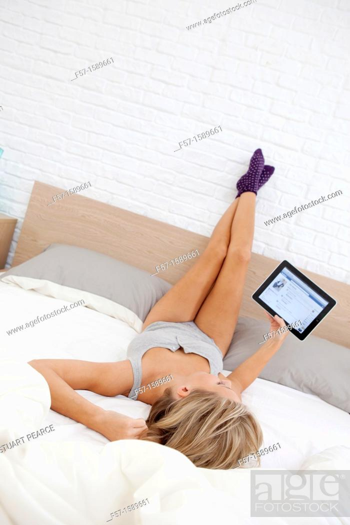 Stock Photo: Young woman relaxing on her bed on her tablet computer.