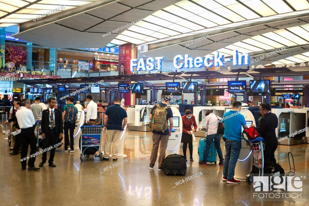 Stock Photo: Singapore, Republic of Singapore, Asia - Air travellers at the fast check-in area with electronic self check-in kiosks at Changi Airport Terminal 2.