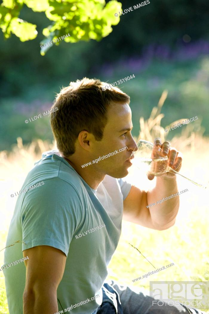 Stock Photo: A young man sitting on the grass, drinking wine.