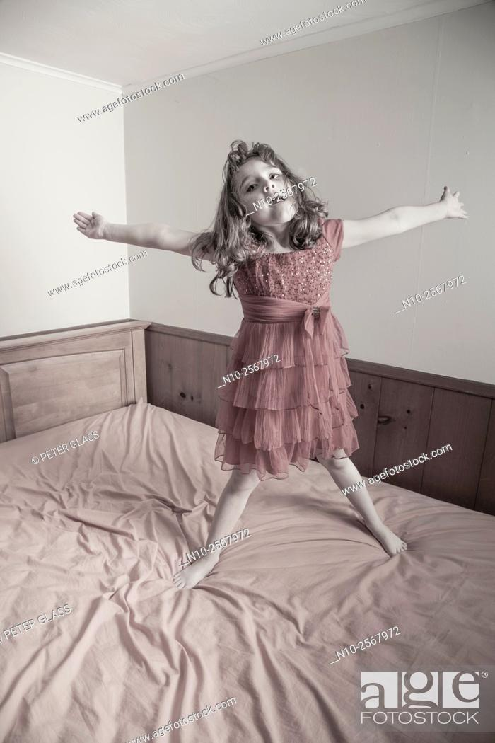 Stock Photo: Six year old girl on her bed.