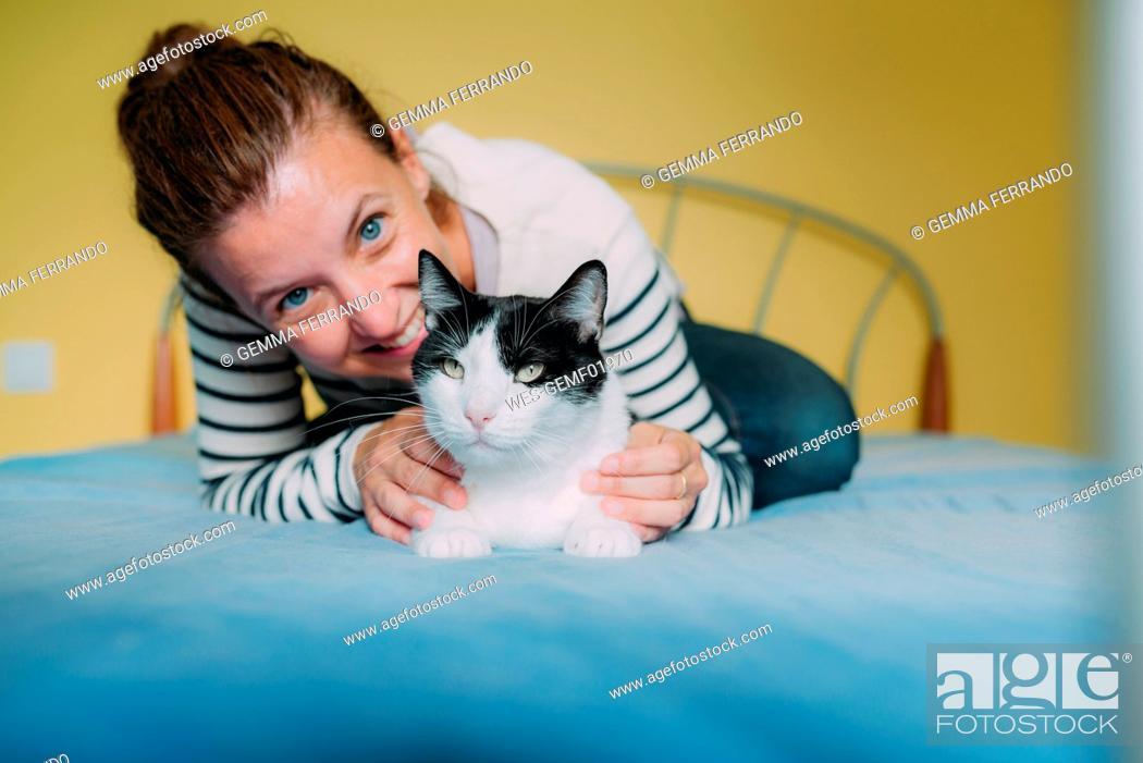 Stock Photo: Happy woman with a black and white cat on the bed.