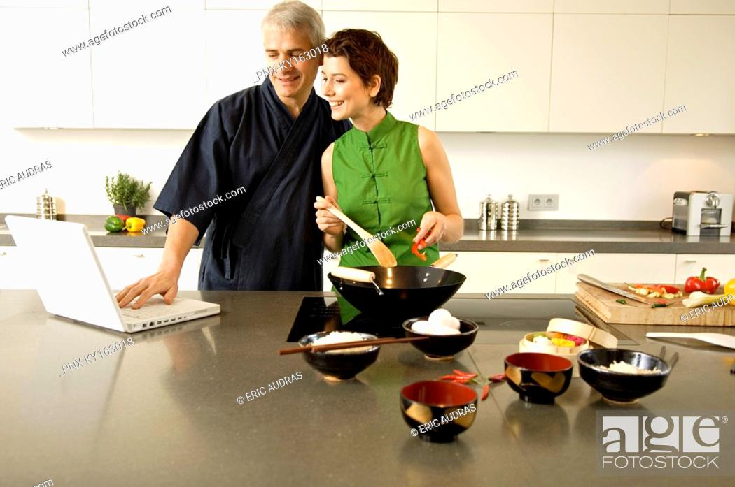 Stock Photo: Mid adult woman preparing food with a mature man using a laptop in the kitchen.