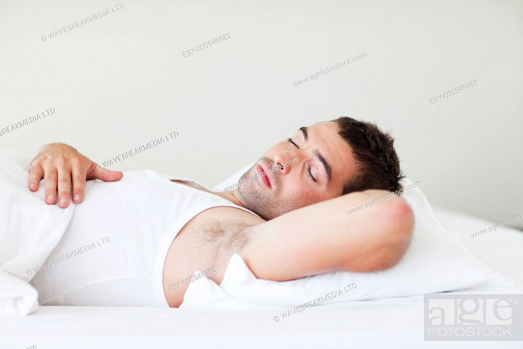 Stock Photo: Young man sleeping in bed.