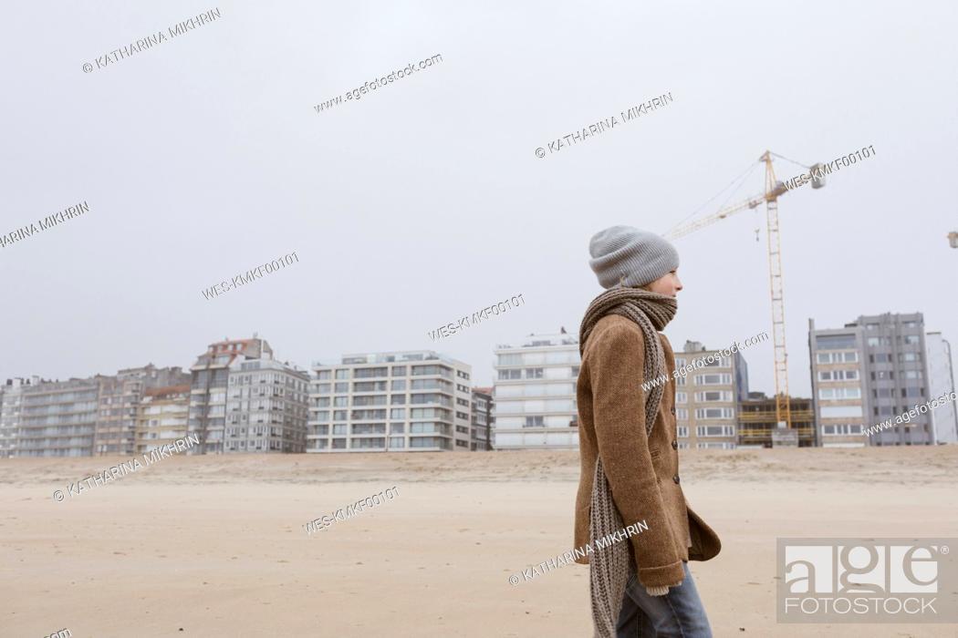 Stock Photo: Germany, North Sea Coast, boy strolling on the beach in winter.