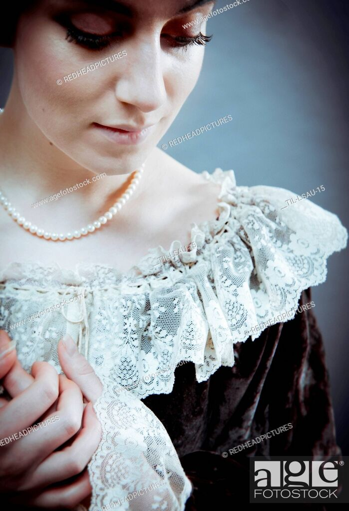 Stock Photo: Young woman with short brown hair wearing period dress with lace collar and pearl necklace.