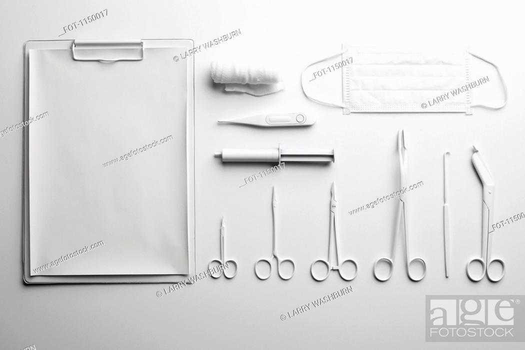 Stock Photo: Clipboard, various medical scissors and instruments painted white and arranged neatly.
