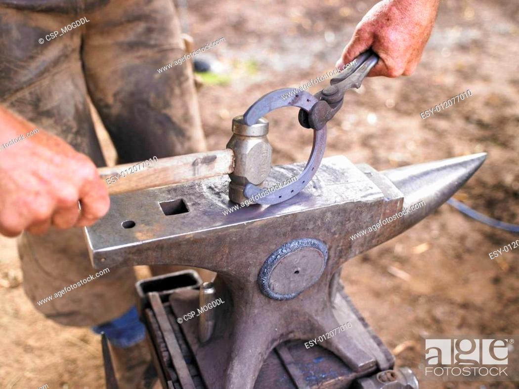 Stock Photo: Farrier Holding Hammer and Horseshoe on Anvil.