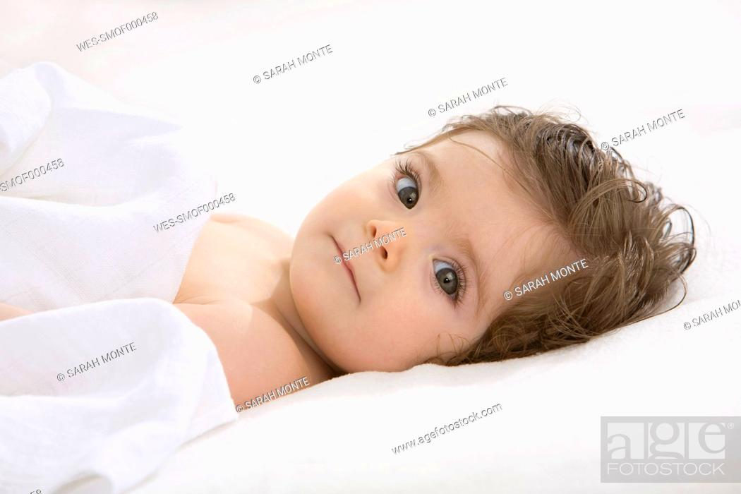 Stock Photo: Baby girl lying on back, covered with blanket, portrait.