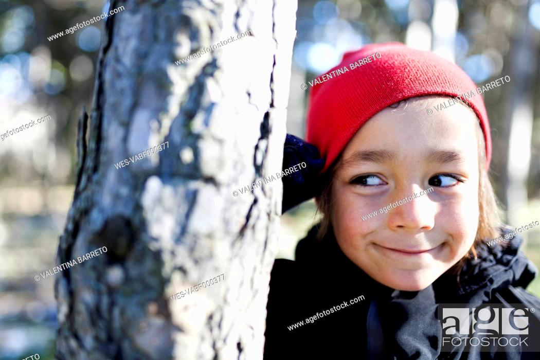 Stock Photo: Portrait of smiling little boy hiding behind a tree trunk.