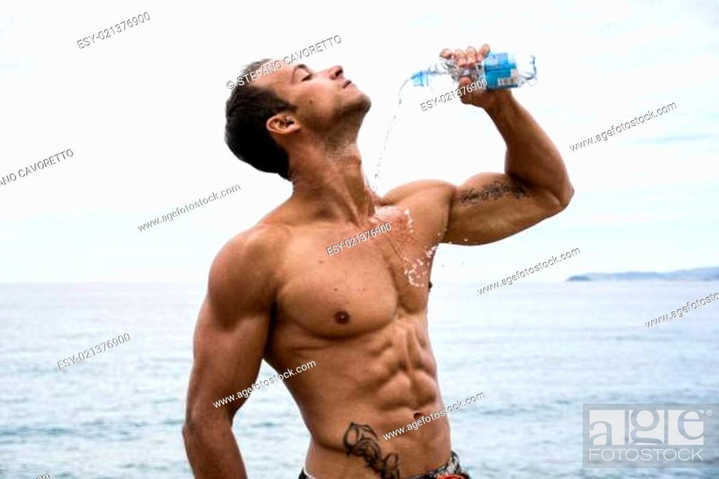 Stock Photo: Attractive shirtless muscleman on the beach pouring water on himself.