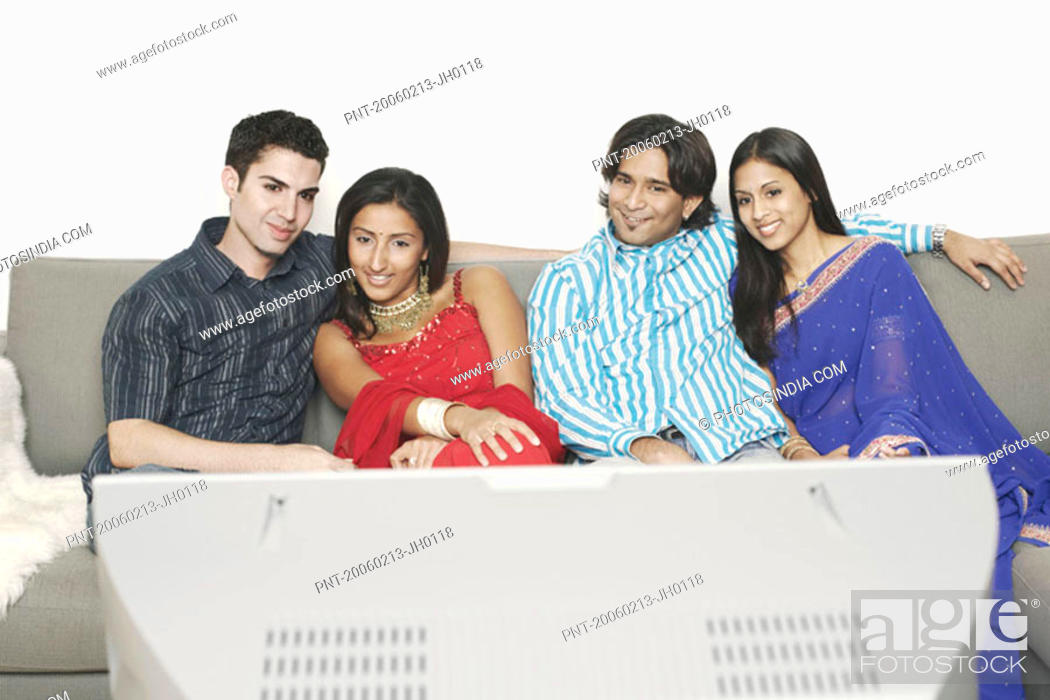 Stock Photo: Two young couples sitting on a couch and watching television.
