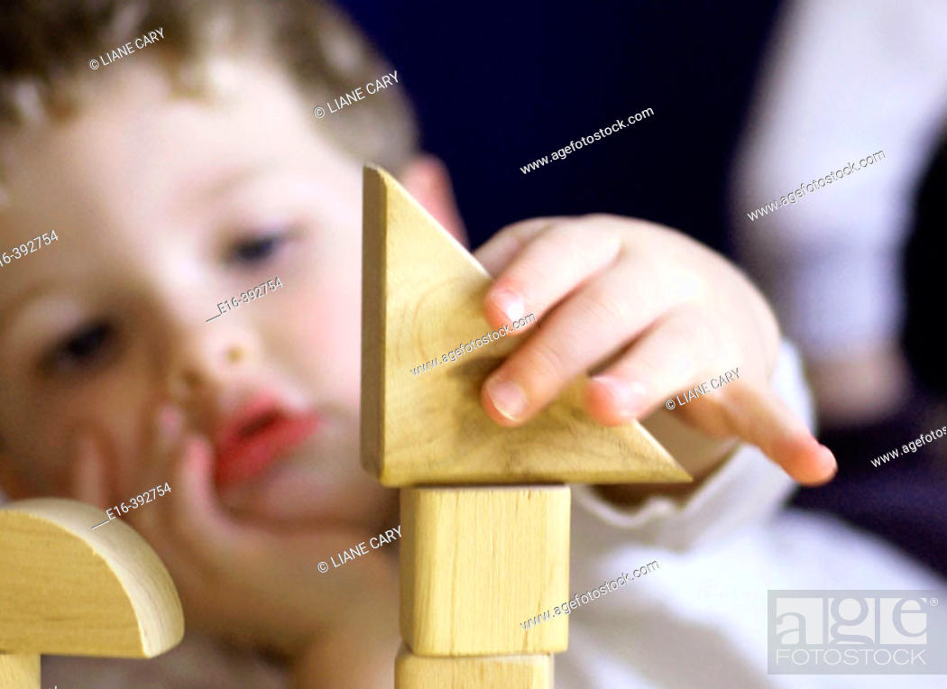 Stock Photo: Boy concentrating on building blocks.