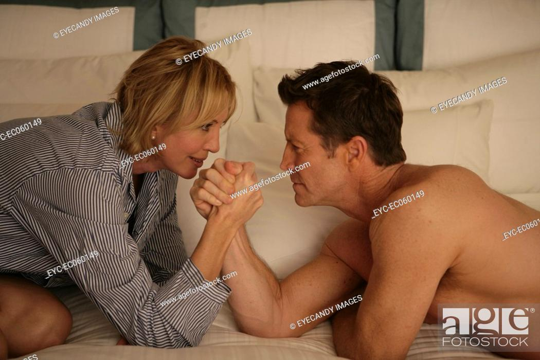 Stock Photo: Mature couple arm wrestling in bed.