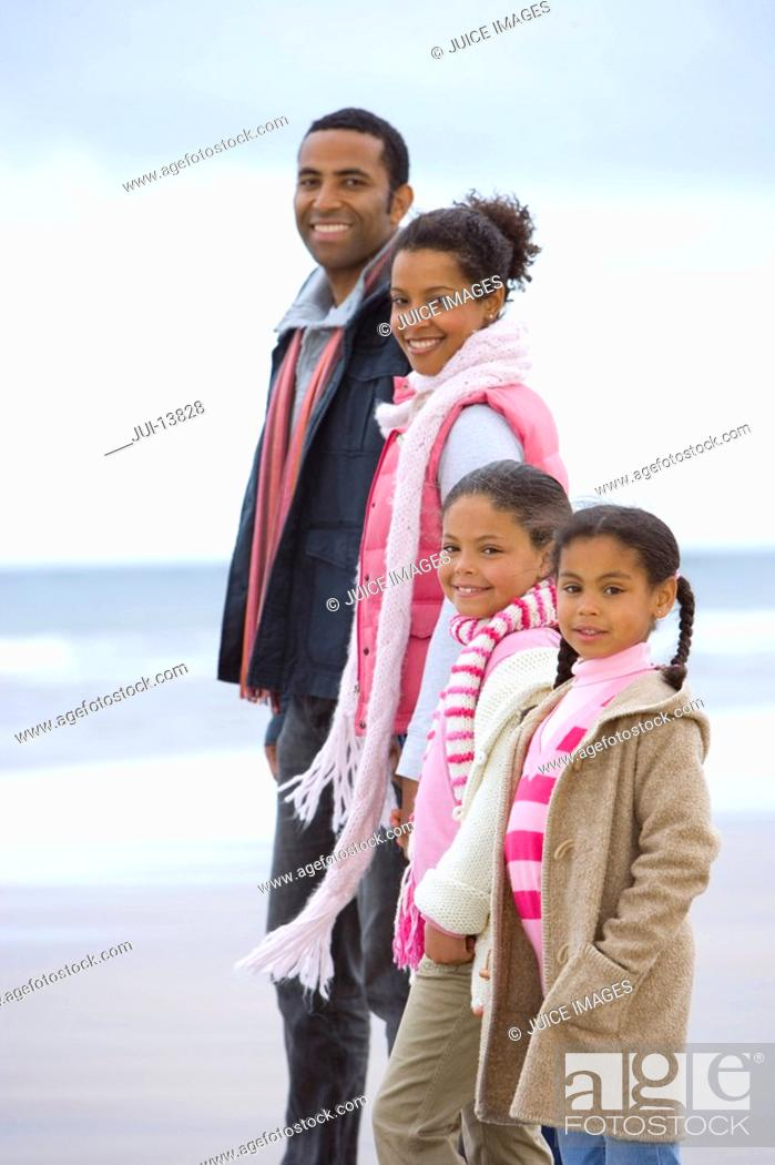 Stock Photo: Family of four in row on beach, smiling, portrait.