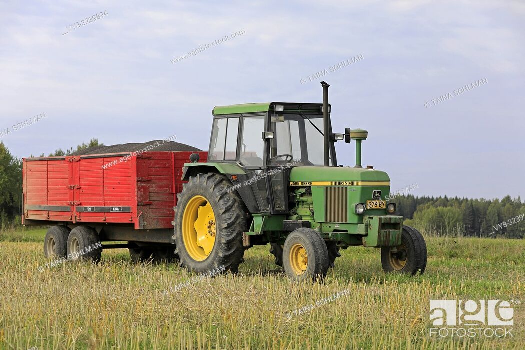 Stock Photo: Salo, Finland - September 8, 2018: John Deere 3140 farm tractor and agricultural trailer full of harvested rapeseed on a beautiful day of autumn.