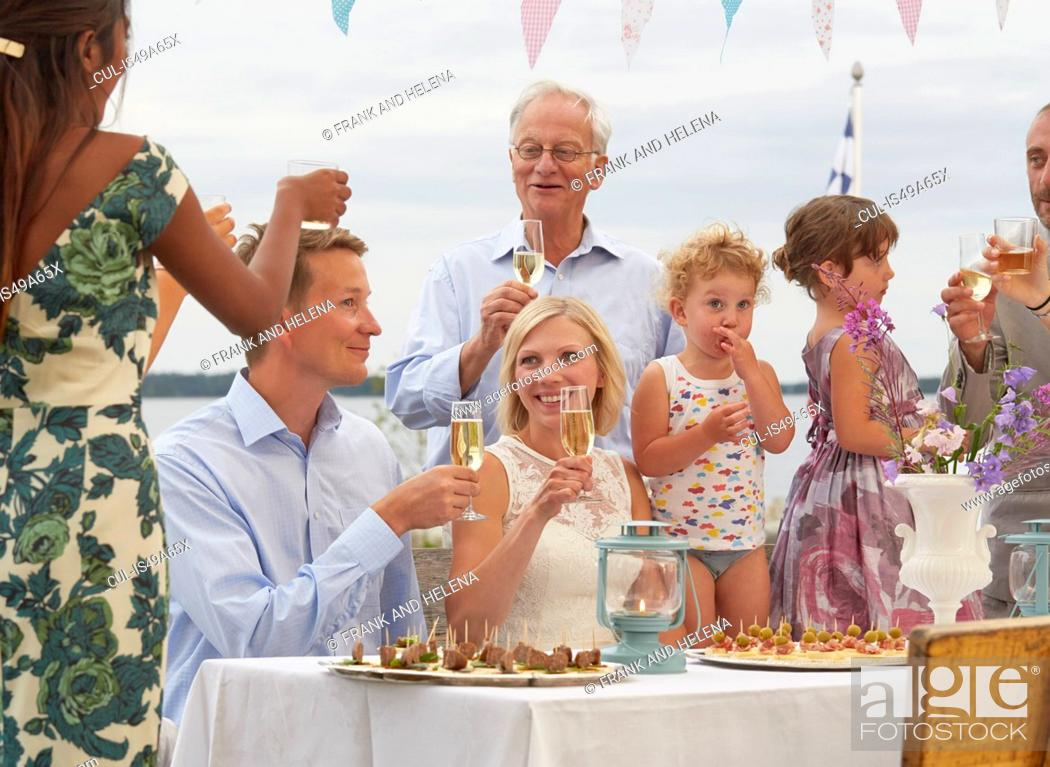 Mid Adult Couple At Wedding Reception Making A Toast With Friends