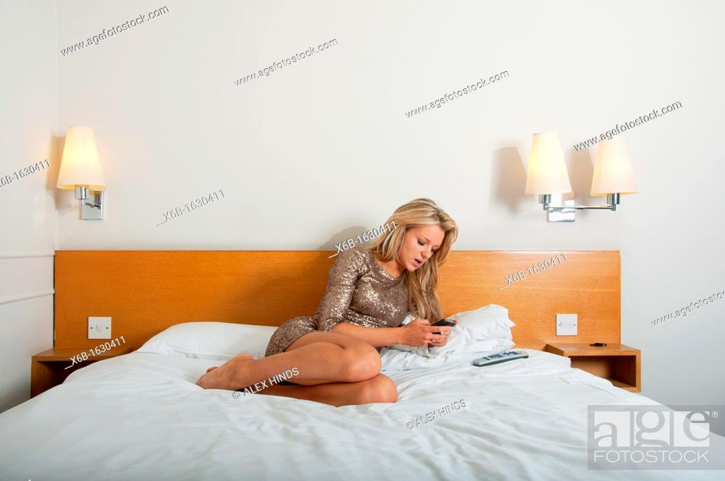 Stock Photo: Young woman, 18-25 years, using smartphone in a hotel room.