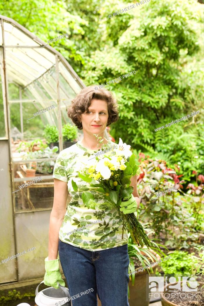 Stock Photo: Woman holding flowers in garden.