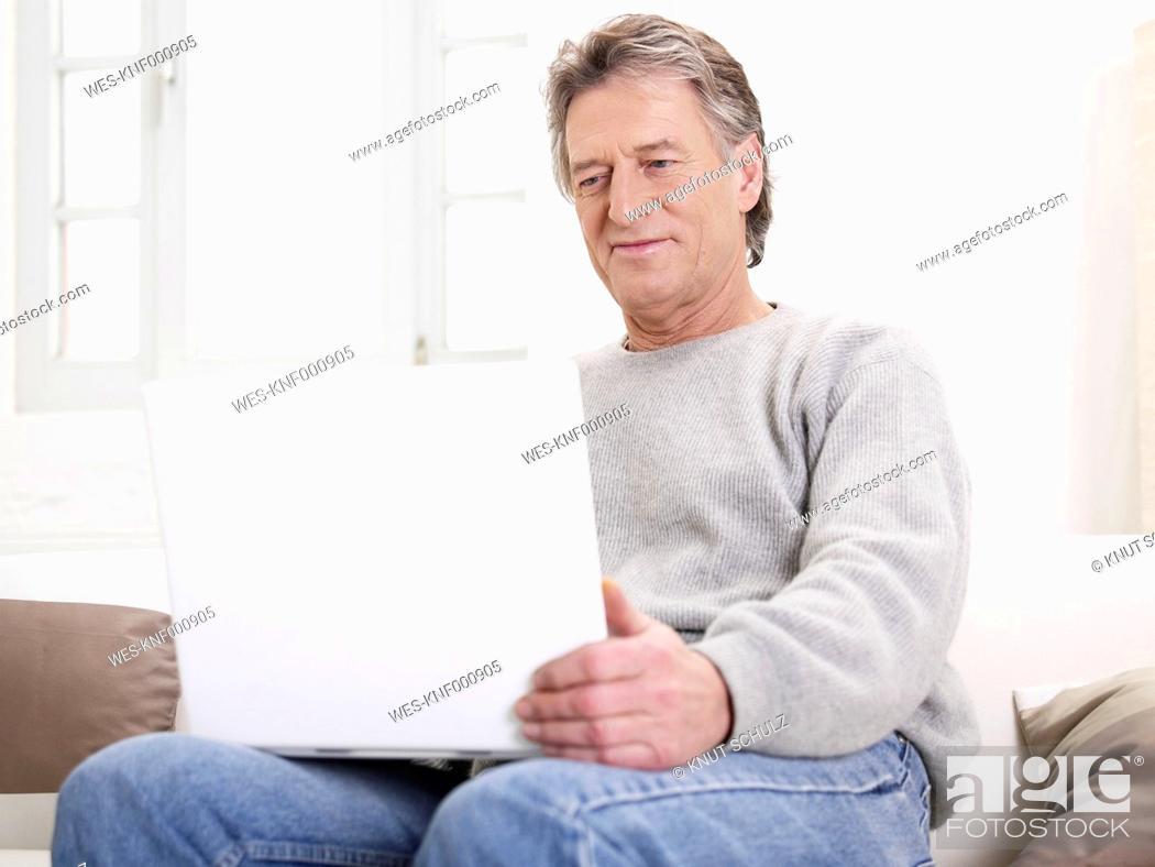 Stock Photo: Germany, Hamburg, Senior man using laptop.