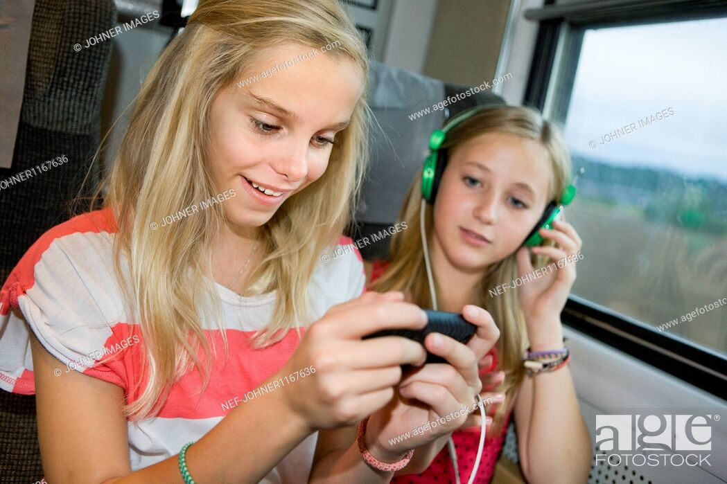 Stock Photo: Twin sisters traveling on high speed train.