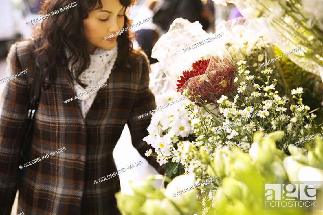 Stock Photo: Woman looking at flowers.