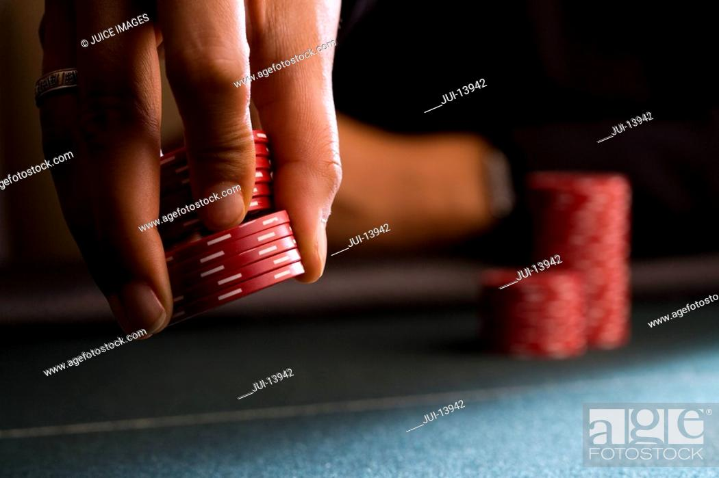 Stock Photo: Woman placing gambling chips on table, close-up.