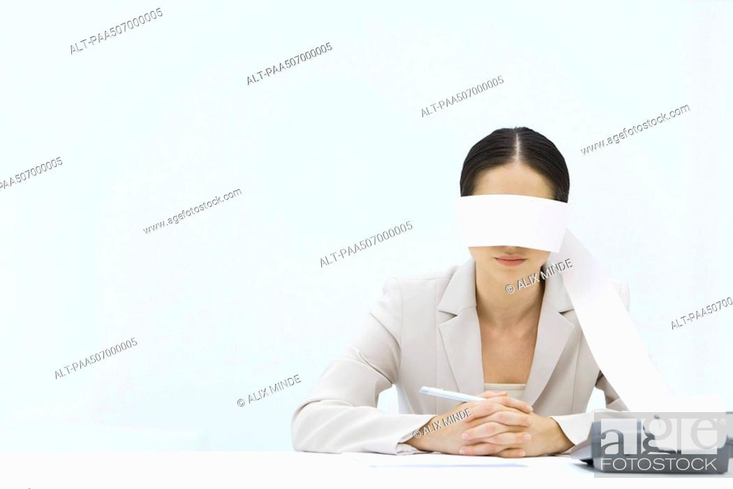 Stock Photo: Woman sitting at table with adding machine tape wrapped around her eyes.