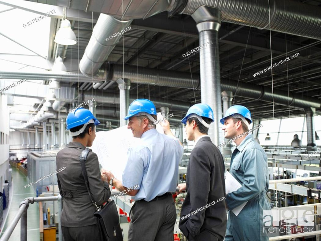 Stock Photo: Businesspeople in hard-hats looking at blueprints.