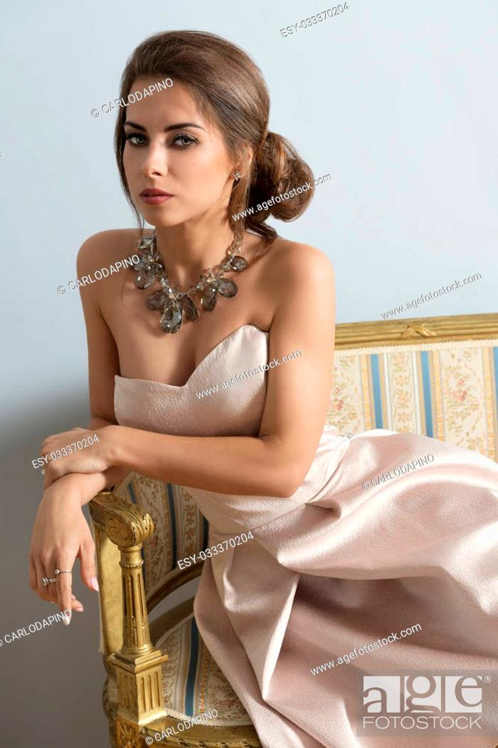 Imagen: elegant brunette girl with rich style posing with elegant pink dress and precious necklace on old sofa in indoor portrait.