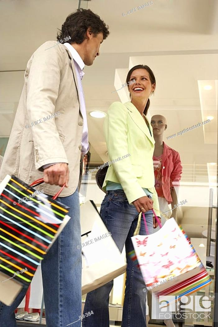 Stock Photo: Couple walking past window display in clothes shop, carrying shopping bags, smiling, low angle view.