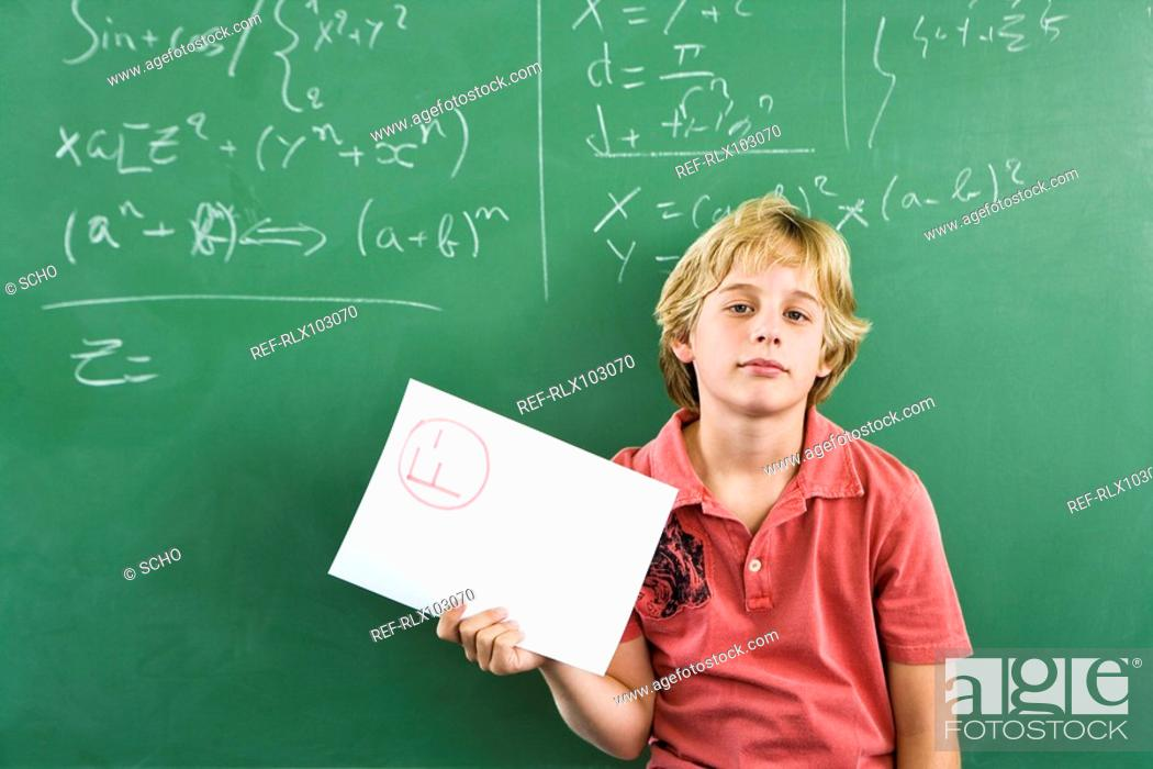 Stock Photo: School boy 10-13 in classroom standing in front of blackboard with test result.