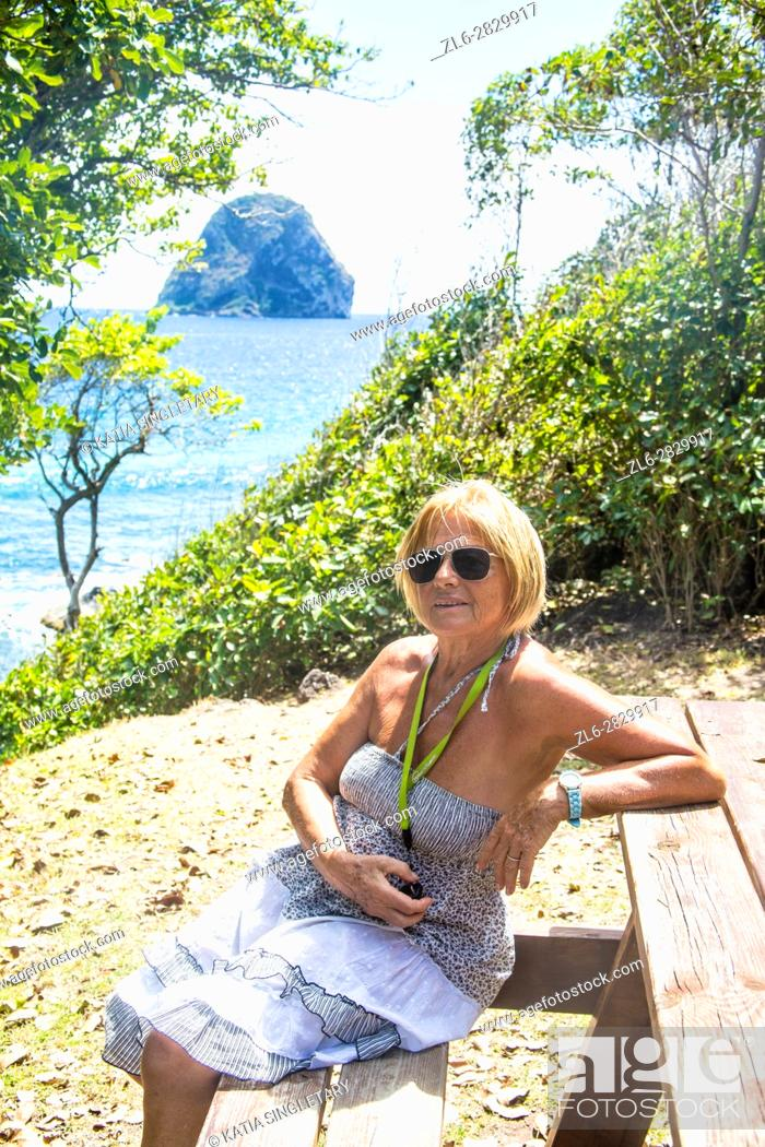 Stock Photo: Caucasian senior matured blond woman playing on her cellular phone, and texting while on vacation by the sea in Martinique.