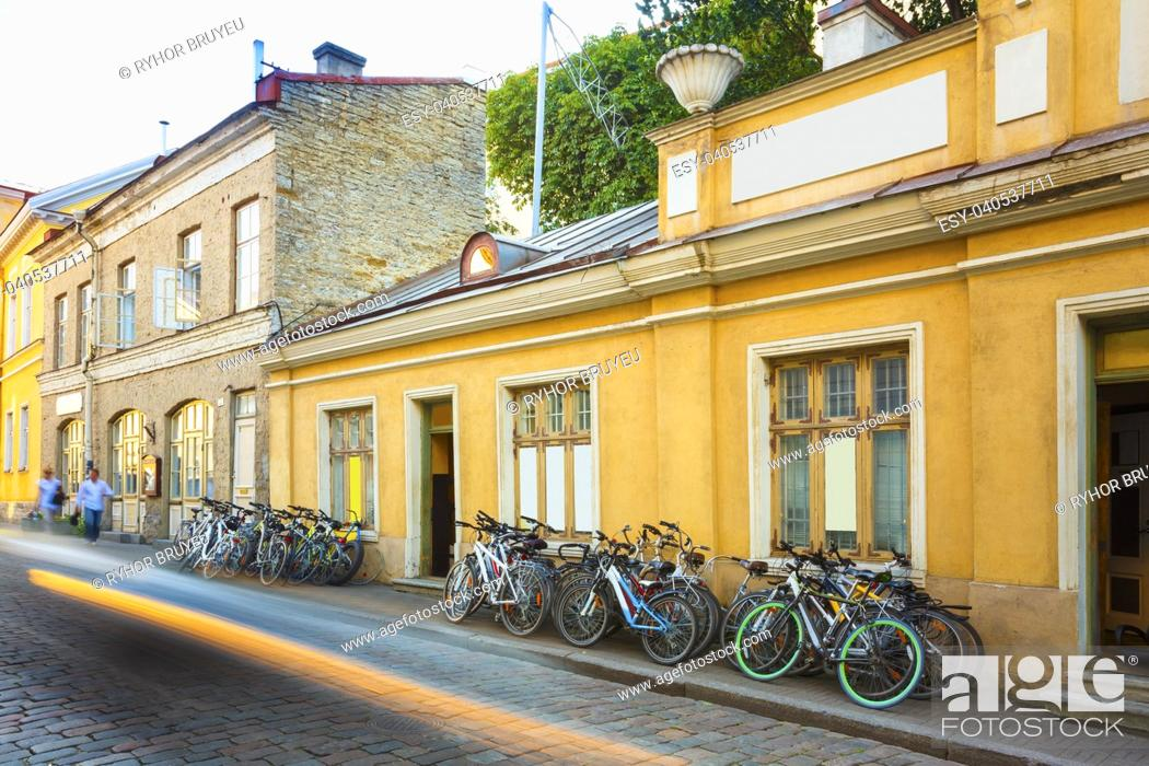 Stock Photo: Tallinn, Estonia. Bicycles Rental Bikes Parking Near Old House In Old Part Town In Summer Evening. Bicycle Tourism.