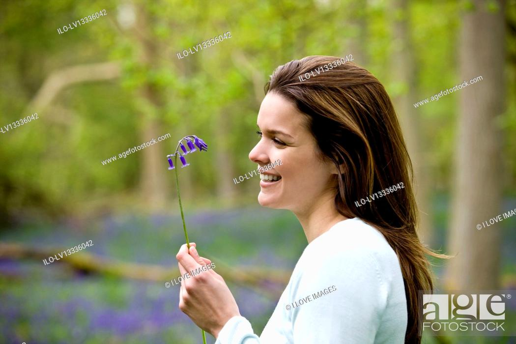 Stock Photo: Portrait of a young woman holding a bluebell.