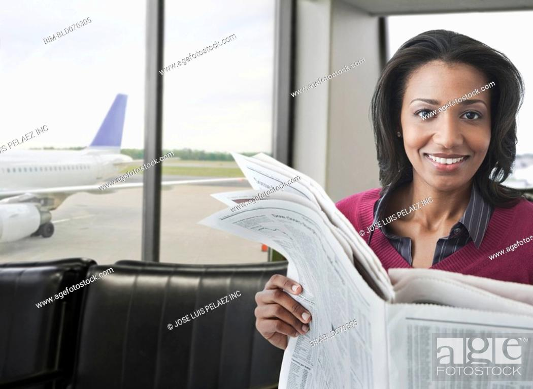 Stock Photo: Smiling African woman reading newspaper in airport lounge.