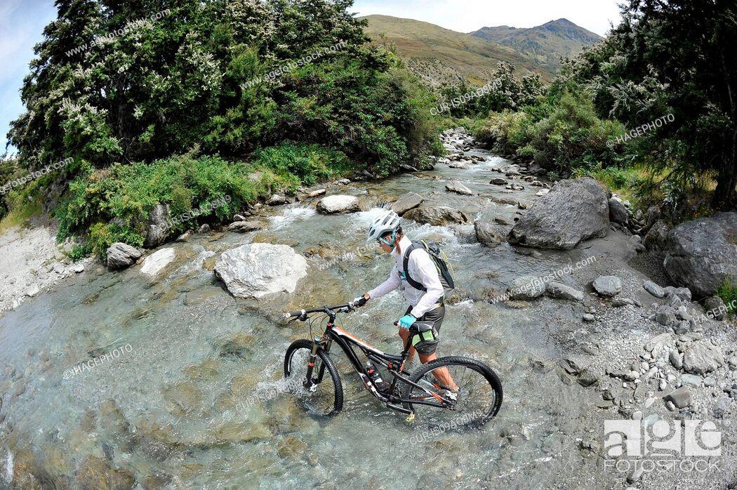 Imagen: Woman pushing mountain bike through water, New Zealand.