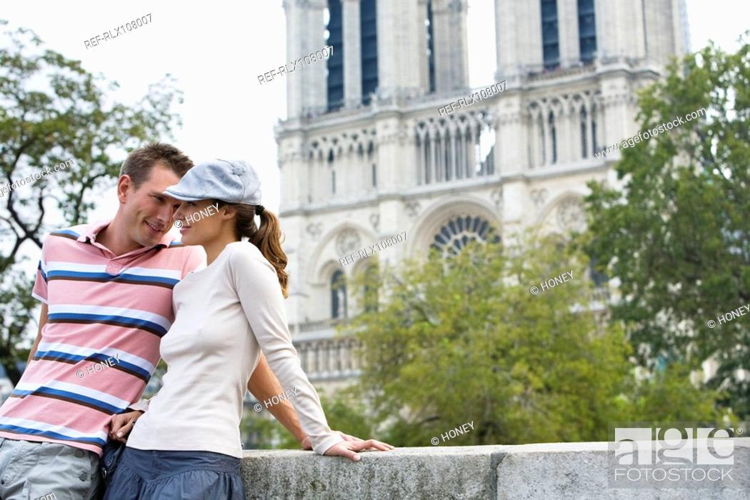 Stock Photo: Young couple enjoying view in front of Notre Dame Cathedral, Paris, France.