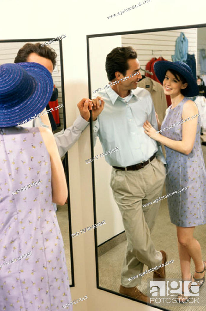 Stock Photo: Mid adult couple standing in front of a mirror in the fitting room of a clothing store.