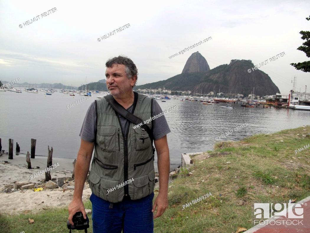 Stock Photo: Biologist Mario Moscatelli standing in rubbish by the Canal do Fundao north of Rio de Janeiro, Brazil, 10 March 2015. Moscatelli warns against going into the.