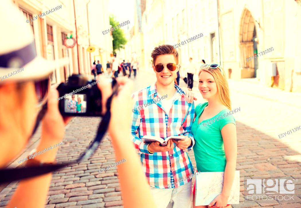 Stock Photo: travel, vacation, technology and friendship concept - smiling couple with map and photo camera exploring city.
