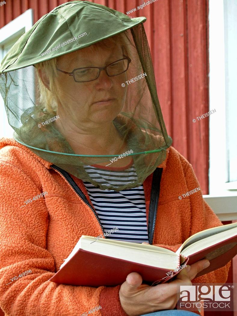 Stock Photo: woman wearing a hat with gaze as protection against gnats mosquitos sitting in front of a red scandinavian timber wooden house reading a book.