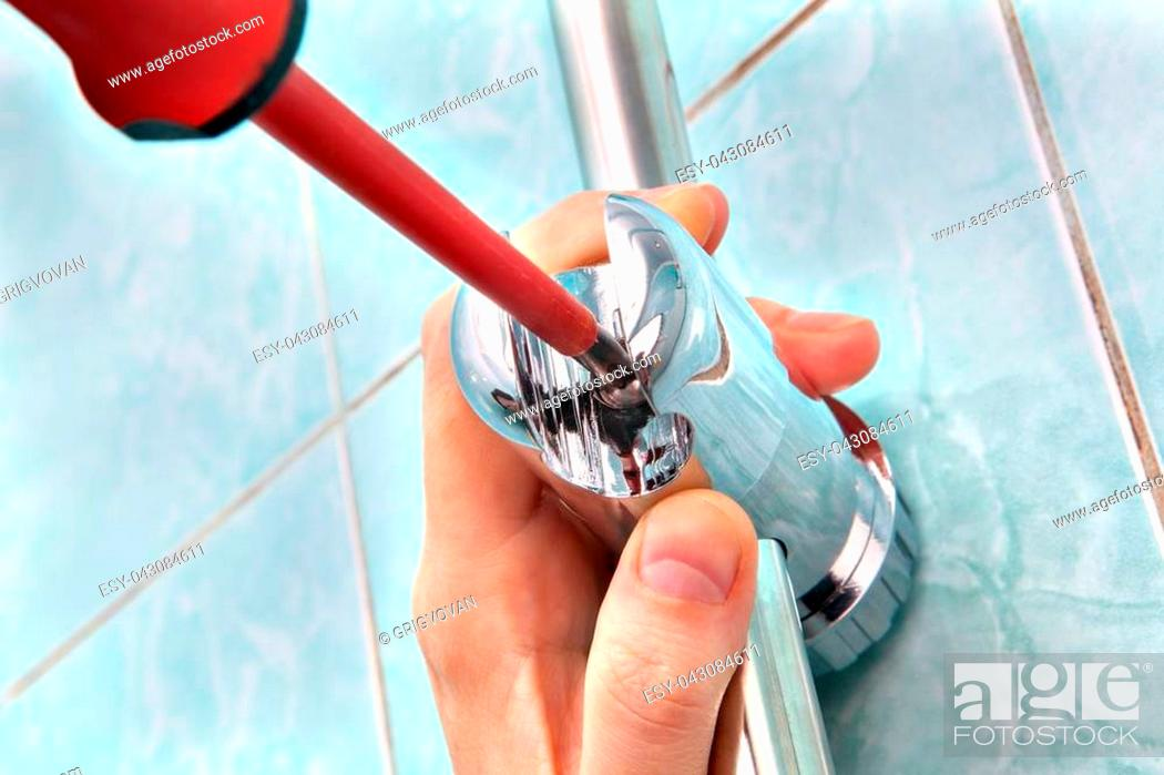Stock Photo: Residential plumbing repair, replacing the plumbing in the bathroom, close-up of hands handyman with red phillips screwdriver.