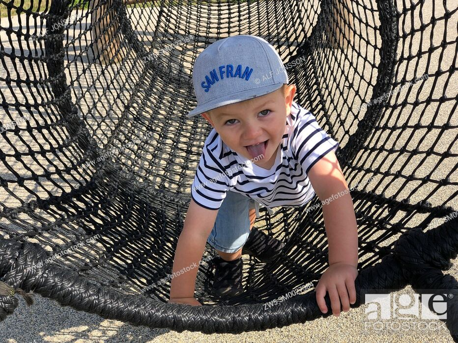 Stock Photo: Boy, thee years old, plays in a net on a playground in Ystad, Sweden, Scandinavia.