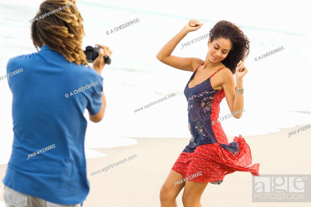 Stock Photo: Man making a video of a dancing woman on the beach.