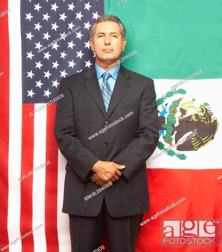 Stock Photo: Hispanic businessman in front of American and Mexican flags.